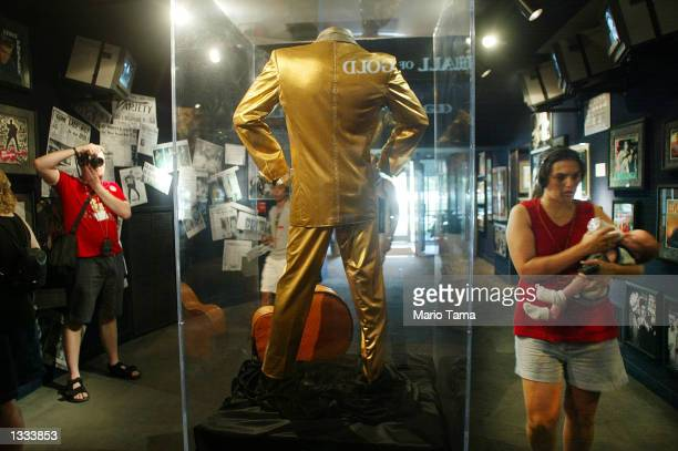 Fan photographs Elvis Presley's famous gold lame' suit on display at Graceland during Elvis Week on August 12, 2002 in Memphis, Tennessee. 75,000...