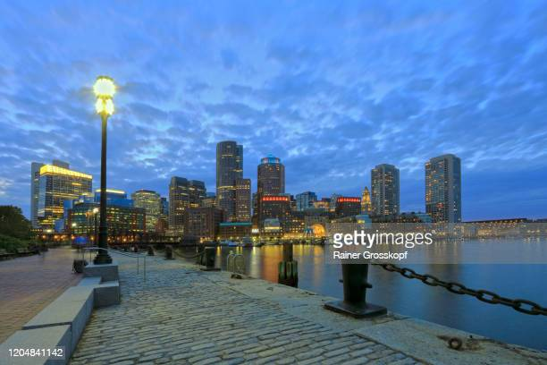 fan pier across the water at the skyscrapers of boston harbor at dusk - rainer grosskopf stock pictures, royalty-free photos & images