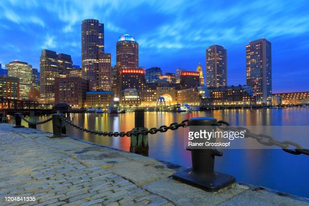 fan pier across the water at the skyscrapers of boston harbor at dusk - rainer grosskopf foto e immagini stock