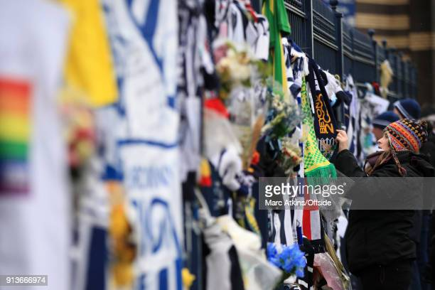 A fan places a scarf on the Jeff Astle gates as a tribute to the late Cyrille Regis prior to the Premier League match between West Bromwich Albion...