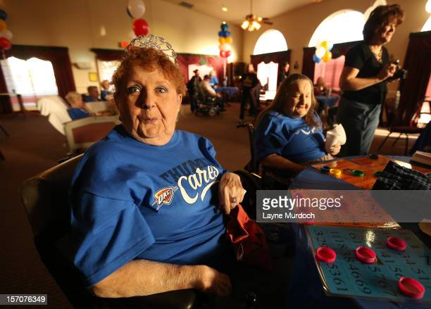 A fan plays bingo as Oklahoma City Thunder players Reggie Jackson Jeremy Lamb and Nick Collison take part in a Thunder holiday party tomorrow at...