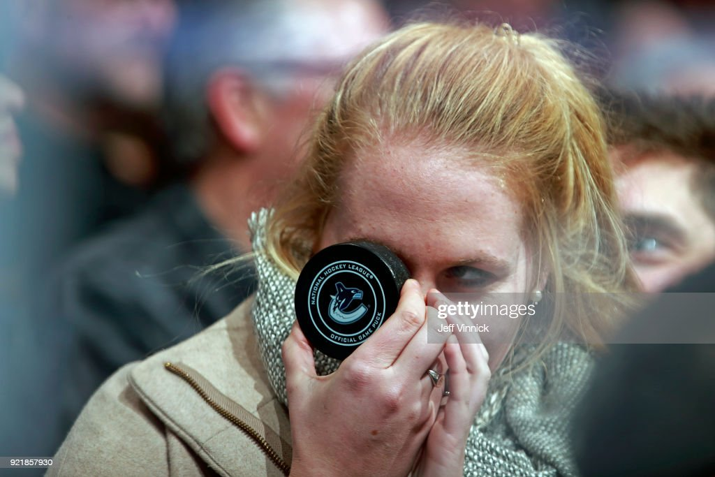 A fan poses for a photo after catching a game puck during their NHL game at Rogers Arena between the Vancouver Canucks and the Colorado Avalanche February 20, 2018 in Vancouver, British Columbia, Canada. Colorado won 5-4.