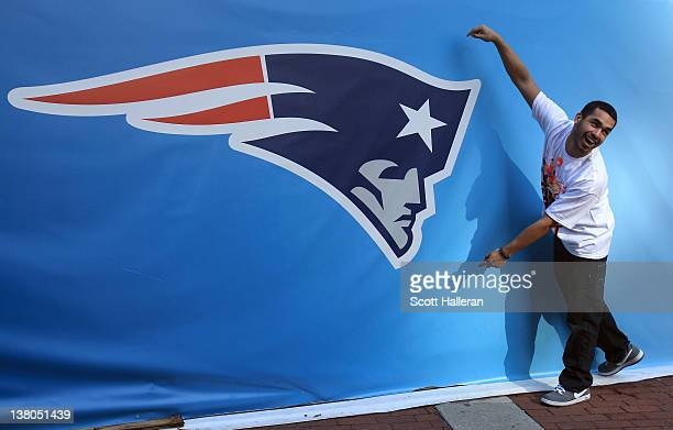A fan poses for a photo next to a giant New England Patriots logo prior to Super Bowl XLVI between the New York Giants and the New England Patriots...