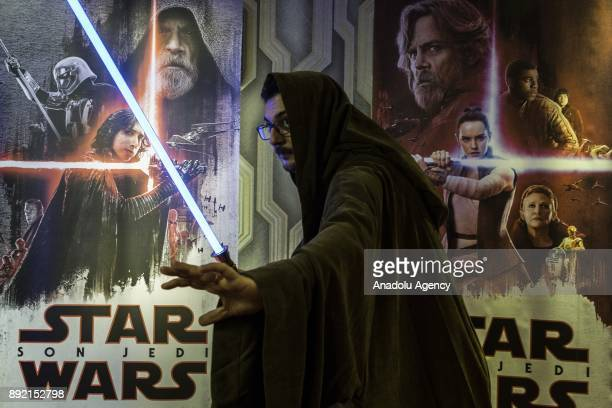 A fan poses for a photo with a lightsaber during a gathering for the latest of the Star Wars film series Star Wars The Last Jedi movie in Istanbul...
