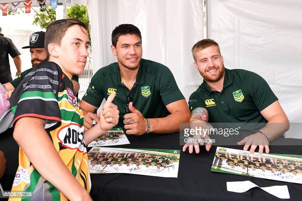 A fan poses for a photo with Jordan McLean and Cameron Munster of the Kangaroos during an Australia Kangaroos and England Signing Session at...