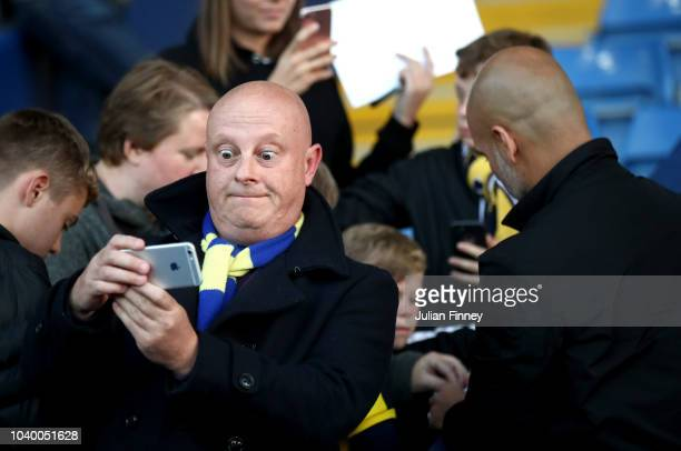 A fan poses for a selfie with Josep Guardiola Manager of Manchester City prior to the Carabao Cup Third Round match between Oxford United and...