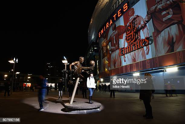 A fan poses for photographs next to the Dennis Bergkamp statue prior to the Barclays Premier League match between Arsenal and Southampton at the...