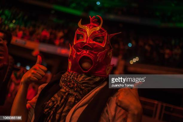 A fan poses for pictures wearing a wrestling mask during an AAA World Wide Wrestling match on November 16 2018 in Bogota Colombia