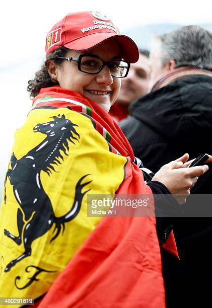 A fan poses in a Ferrari flag as wellwishers hold a vigil for the former German Formula One driver Michael Schumacher at the Grenoble University...