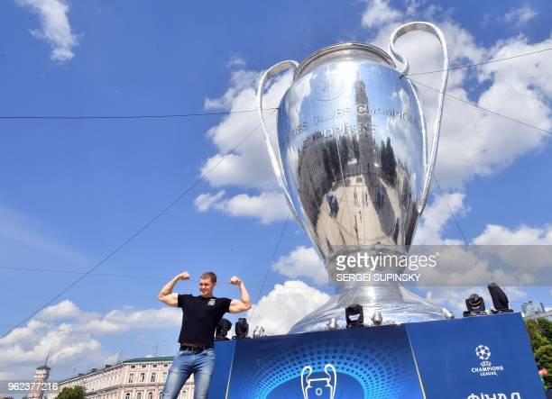 A fan poses in front of a huge trophy set in the Ukrainian capital of Kiev on May 25 a day before of the 2018 UEFA Champions League Cup final...