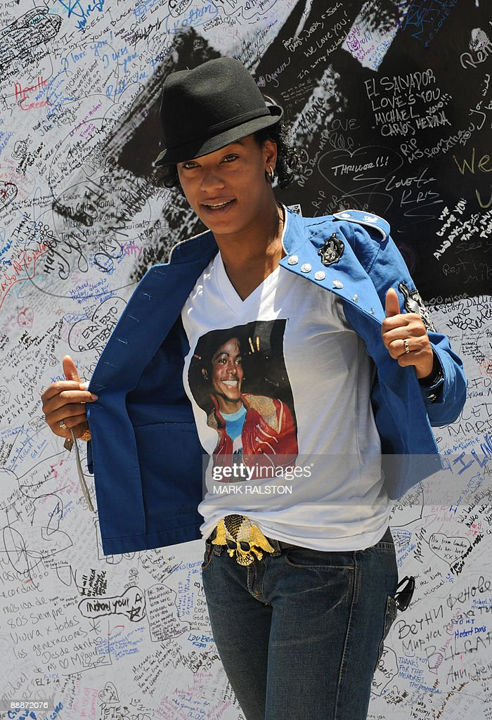 A fan poses in front of a Michael Jackson poster covered in messages outside the Staples Center, which will be the site of a memorial service for musical legend after his recent death, in Los Angeles on July 6, 2009. A total of 1.6 million people scrambled for tickets to Jackson's memorial service, officials said as the probe into the singer's death zeroed in on the role of drugs. The vast majority of applicants will be disappointed as only 11,000 tickets are available for Tuesday's service, along with another 6,500 to watch a live video feed at a neighboring venue. AFP PHOTO/Mark RALSTON
