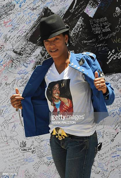 Fan poses in front of a Michael Jackson poster covered in messages outside the Staples Center, which will be the site of a memorial service for...