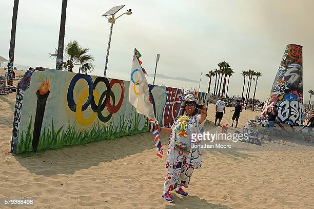 A fan poses in front of the Olympic Rings torch and Team USA logo during the Team USA Send Off Event on July 23 2016 in Venice California