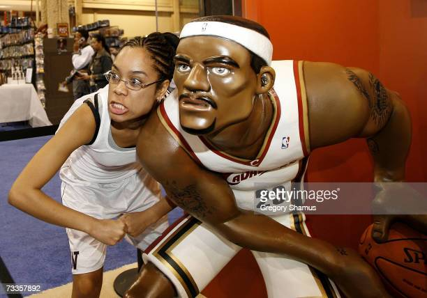 Fan poses next to a LeBron James statue at the Jam Session during NBA All Star Weekend on February 17, 2007 in Las Vegas, Nevada. NOTE TO USER: User...