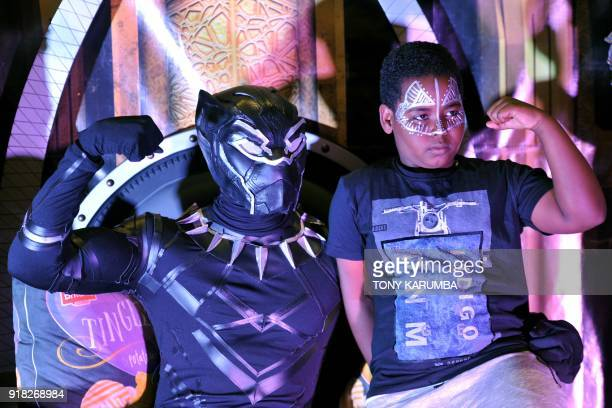 A fan poses with a cosplayer portraying a character from the 2018 US superhero film based on the Marvel Comics character 'The Black Panther' pose in...