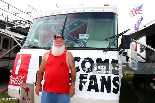 A fan poses with a Darlington Raceway program from 1976 in the campgrounds during qualifying for the Monster Energy NASCAR Cup Series Bojangles'...