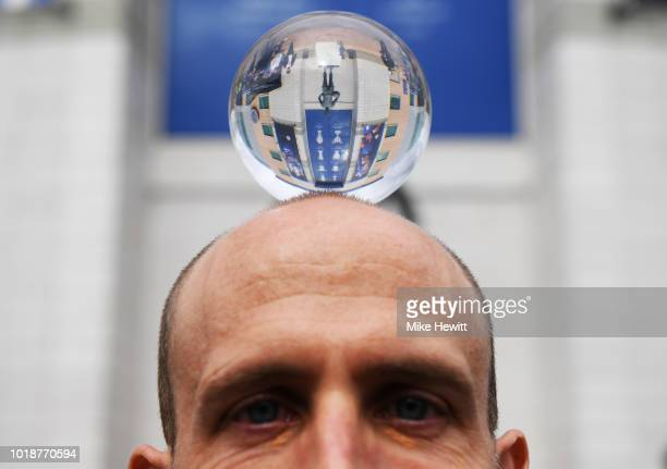 A fan poses with a glass ball of the stadium reflection prior to the Premier League match between Chelsea FC and Arsenal FC at Stamford Bridge on...