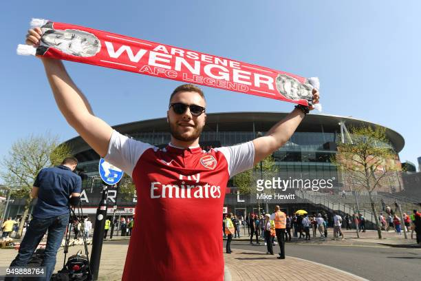 A fan poses with merchandise prior to the Premier League match between Arsenal and West Ham United at Emirates Stadium on April 22 2018 in London...