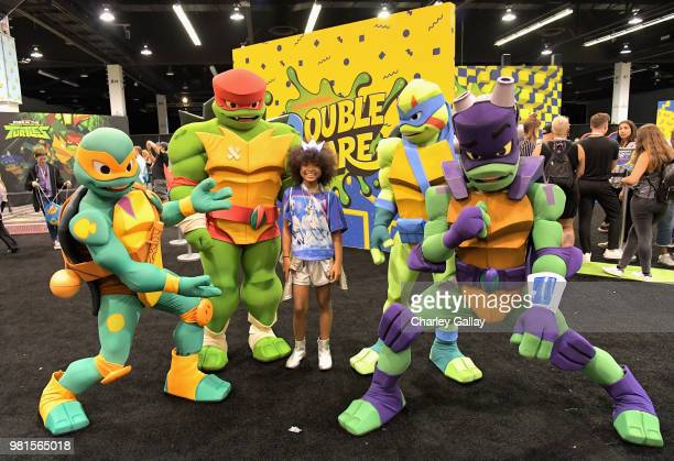 A fan poses with Nickelodeon's 'Rise of the Teenage Mutant Turtles' costumed characters at Nickelodeon's booth at 2018 VidCon at Anaheim Convention...