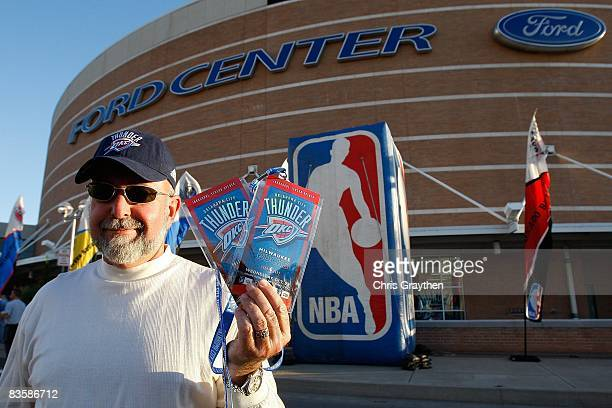A fan poses with tickets to opening night between the Milwaukee Bucks and the Oklahoma City Thunder at the Ford Center on October 29 2008 in Oklahoma...