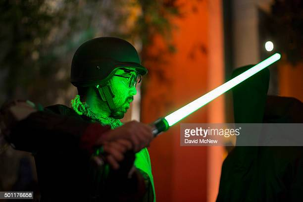 A fan practices light saber fighting technique as people camp out in the TLC Chinese Theatre courtyard for the premiere of Walt Disney Pictures And...