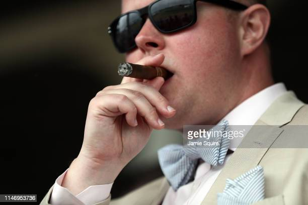 Fan puffs on a cigar while watching horses cross the line during the Humana Distaff prior to the 145th running of the Kentucky Derby at Churchill...
