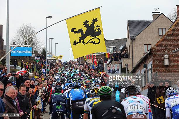 A fan raises a Vlaamse Leeuw flag as the peloton passes during the 97th edition of the Tour of Flanders on March 31 2013 in Brugge Belgium