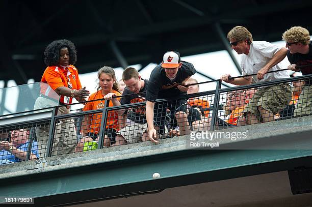 A fan reaches for a foul ball in the stands during the game between the Baltimore Orioles and the Detroit Tigers at Oriole Park at Camden Yards on...