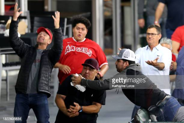 Fan reaches out to catch a foul ball during the sixth inning of a game between the Los Angeles Angels and the Kansas City Royals at Angel Stadium of...