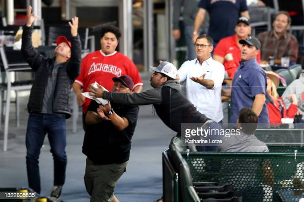 Fan reaches out to catch a foul ball during the sixth inning of a game between the Los Angeles Angels an the Kansas City Royals at Angel Stadium of...