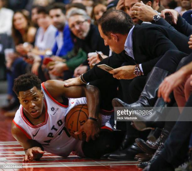 A fan reaches out to give a supportive pat after Toronto Raptors guard Kyle Lowry ended up sliding into the first row on the sideline Toronto Raptors...