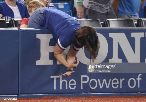A fan reaches over the wall as she tries unsuccessfully to corral a foul ball during the Toronto Blue Jays MLB game against the Tampa Bay Rays at...