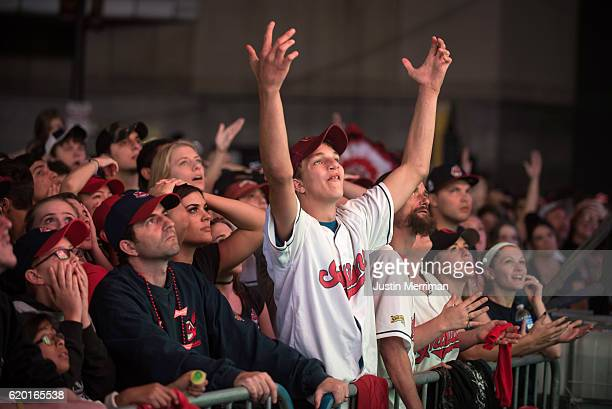 Fan react as the Cleveland Indians give up three runs in the the first inning as they watch on a big screen outside of Progressive Field during game...