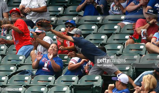 Fan reacts after being stuck in the forehead by a foul ball off the bat of Willie Calhoun of the Texas Rangers as the Rangers play the Detroit Tigers...