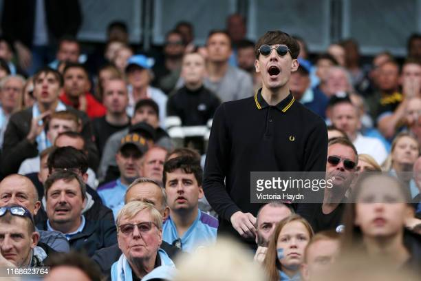A fan reacts during the Premier League match between Manchester City and Tottenham Hotspur at Etihad Stadium on August 17 2019 in Manchester United...