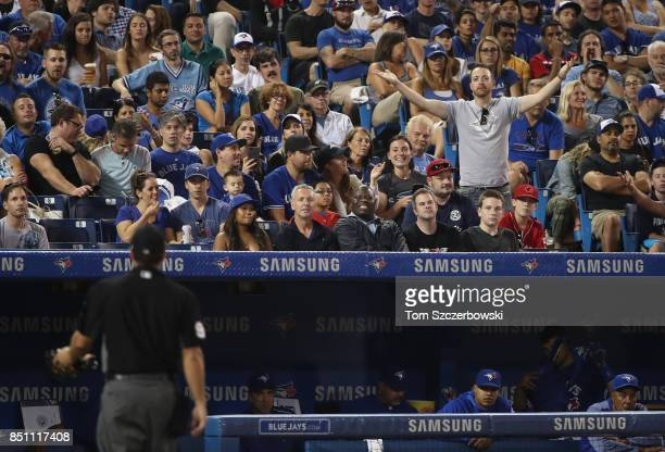Fan reacts towards home plate umpire Ben May after Kevin Pillar of the Toronto Blue Jays was called out on strikes in the fourth inning during MLB...