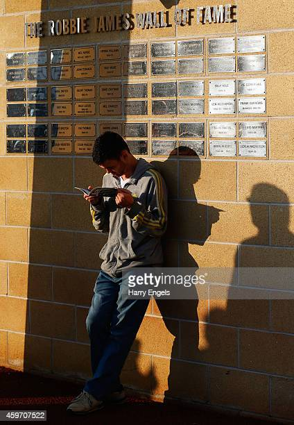 A fan reads a programee next to the Robbie James Wall of Fame prior to the Barclays Premier League match between Swansea City and Crystal Palace at...
