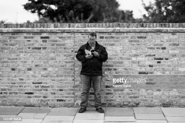 A fan reads a programme outside the stadium prior to the Carabao Cup Second Round match between Fulham and Exeter City at Craven Cottage on August 28...