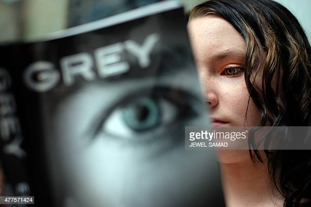 A fan reads her copy of EL James's new book 'Grey Fifty Shades of Grey as Told by Christian' as she wait outside the Barnes and Noble store on Fifth...