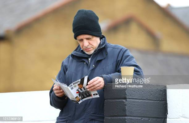 Fan reads the match day programme prior to the Vanarama National League match between Maidenhead United and Stockport County at York Lane on March...