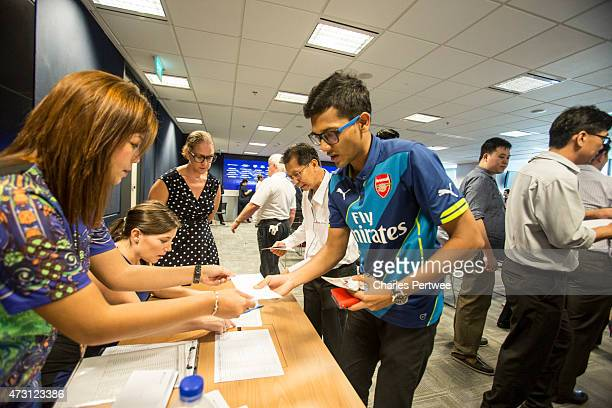 A fan receives one of the first tickets for the tournament during a QA at the Barclays office during the Barclays Asia Trophy 2015 Ticket Launch day...