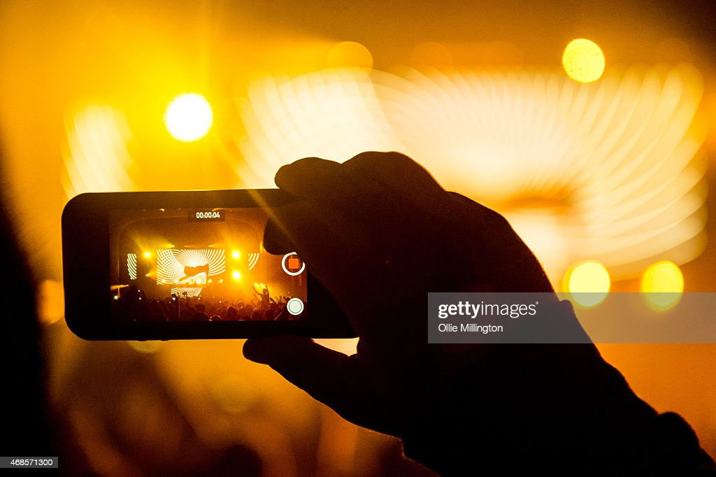 A fan records Above and Beyond performing on stage with a mobile phone during the first of two sold out nights at Brixton Academy on April 3, 2015 in London, United Kingdom.