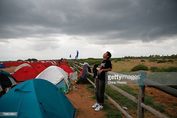 A fan rests in front of tents at the first 'Green Flag Erdos Grassland Rock Music Festival' near the Mausoleum of Genghis Khan on July 22 2007 in...