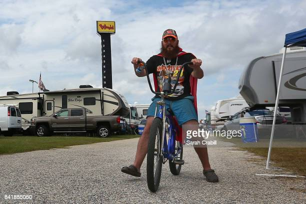 A fan rides his bike through the campgrounds during qualifying for the Monster Energy NASCAR Cup Series Bojangles' Southern 500 at Darlington Raceway...