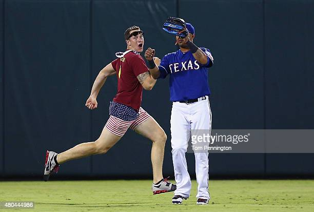 A fan runs across the field past Leonys Martin of the Texas Rangers in the top of the eighth inning at Globe Life Park in Arlington on July 11 2015...