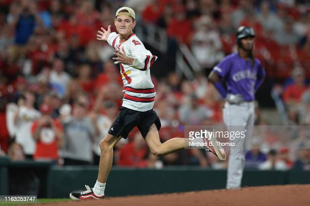 Fan runs into the field of play during a game between the St. Louis Cardinals and the Colorado Rockies at Busch Stadium on August 22, 2019 in St....