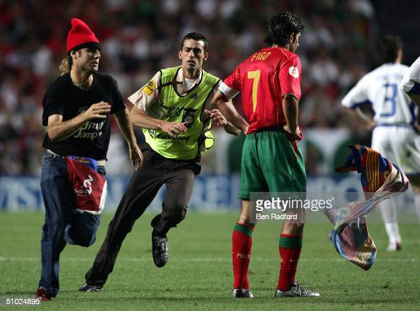 A fan runs on the pitch and throws a Barcelona flag at Luis Figo during the UEFA Euro 2004 Final match between Portugal and Greece at the Luz Stadium...
