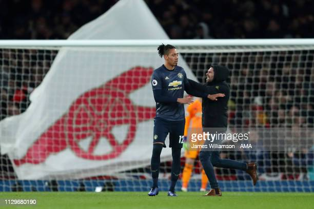 A fan runs onto the pitch and attacks Chris Smalling of Manchester United during the Premier League match between Arsenal FC and Manchester United at...