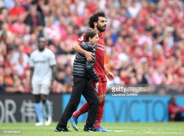 A fan runs onto the pitch and embraces Mohamed Salah of Liverpool during the Premier League match between Liverpool FC and West Ham United at Anfield...