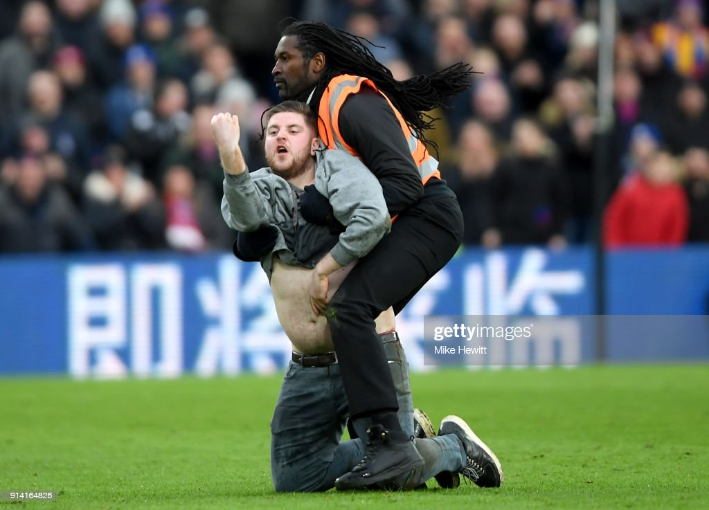 A fan runs onto the pitch and is challenged by a steward during the Premier League match between Crystal Palace and Newcastle United at Selhurst Park on February 4, 2018 in London, England.